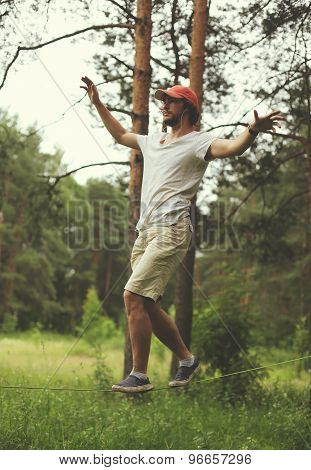 Sport, Leisure, Recreation And Healthy Lifestyle Concept - Man Slacklining Walking And Balancing On