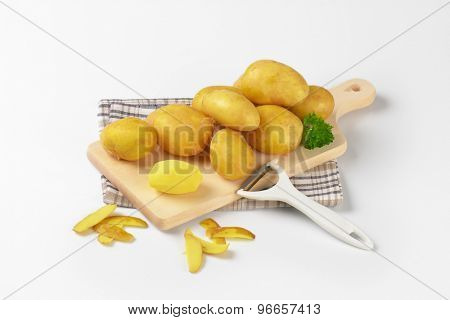 fresh baby potatoes and peeler on wooden cutting board