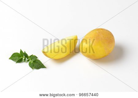 one and quarter baby potato with leaves on white background