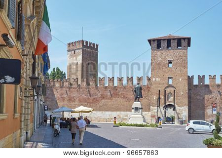 VERONA, ITALY - JULY 11: Pedestrians in front of Castelvecchio castle, with Italian flag in the foreground. July 11, 2015 in Verona.