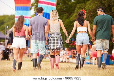 Friends walking together at a music festival site, back view
