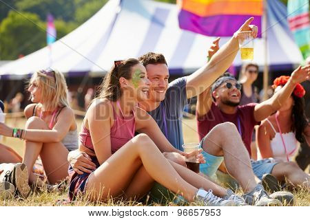 Friends sitting on grass having fun at a music festival
