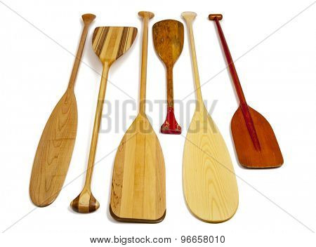 wooden canoe paddles of different shapes and sizes including a classic beaver tail on white background