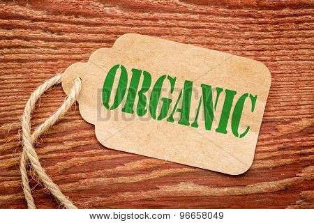 organic sign a paper price tag against rustic red painted barn wood - shopping and healthy lifestyle concept