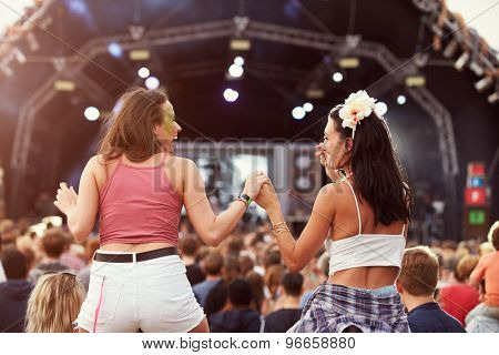 Two girls on shoulders in the crowd at a music festival