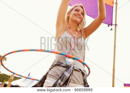 Blonde woman dancing with hula hoop at a music festival