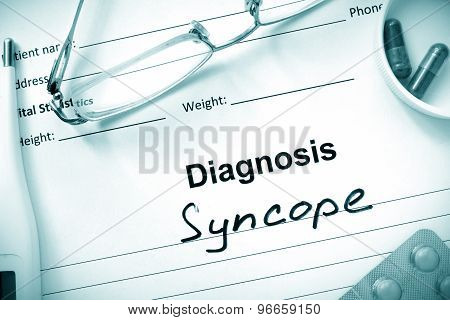 Diagnosis Syncope and tablets on a wooden table.