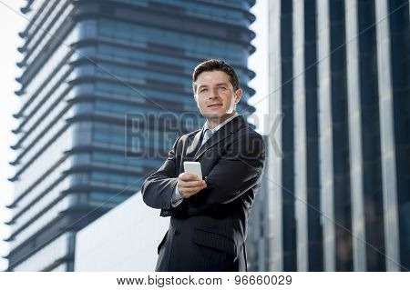 Corporate Portrait Of Young Attractive Businessman With Mobile Phone Outdoors