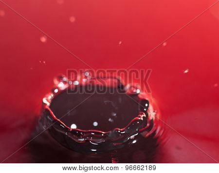 A water droplet hitting the water surface with a red background