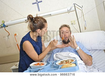 Young Wife Trying To Feed His Reluctant Husband Lying In Bed At Hospital Room Ill After Suffering Ac