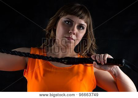Photo of woman in orange dress with whip