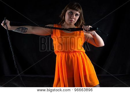 Image of woman in orange dress with whip