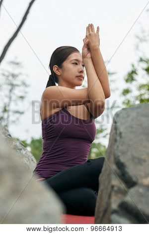 young beautiful woman in advanced yoga sitting posture on the rocks