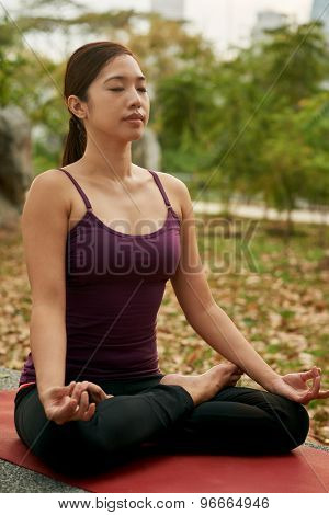 young woman in the park yoga meditating in lotus pose