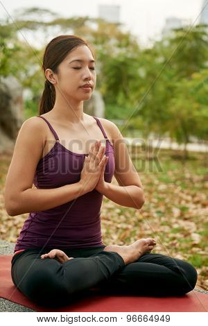 young woman in the park doing yoga pose meditating with praying hands