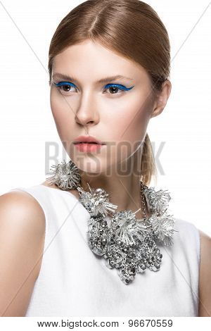 Beautiful fashionable girl with the blue arrows on eyes, smooth hair and original decoration around