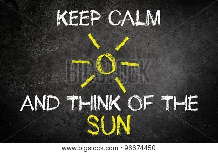 Keep Calm and Think of the Sun Message for Summer Vacation Concept Written on Blackboard with Glowing Sun Drawing.