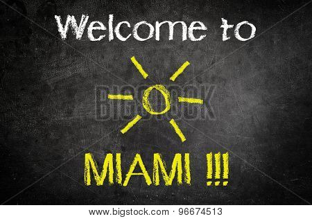 Welcome to Miami Message for Summer Vacation Concept Written on a Black Chalkboard with Glowing Sun Drawing in the Middle.