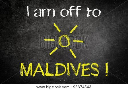 Conceptual I am Off to Maldives Message Written on a Black Vintage Chalkboard with Glowing Sun Drawing in the Middle of the Texts.
