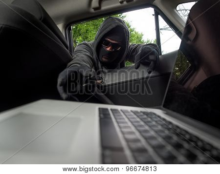 Crime concept - thief stealing laptop from the car. View from laptop