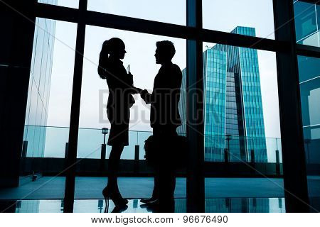 Silhouettes of backlit business people handshake in front of city skyline