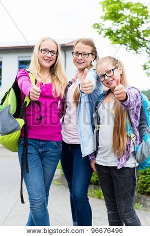 Group of girls standing in front of school