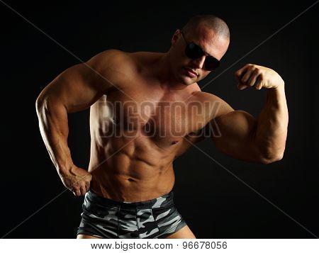 Muscular man shows biceps