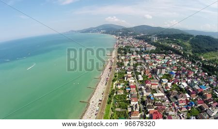 Beach and many houses in coastal city near mountains at summer sunny day. Aerial view. Photo with noise from action camera.