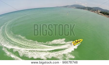 People ride on catamarans and inflatable pad connected to cutter near sea beach at summer sunny day. Aerial view. Photo with noise from action camera.