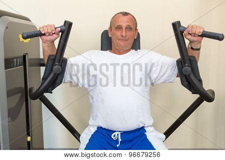 elderly man on a weight machine in the gym