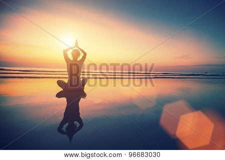 Yoga woman sitting in lotus pose on the beach with reflection in water during amazing sunset.