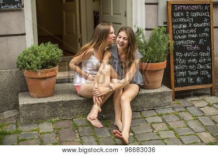 Two young cute girls girlfriend sitting on the steps of the cafe and whispering.