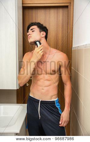 Muscular man shirtless using electric shaver, looking away