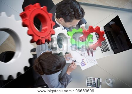 White and red cogs and wheels against sales persons studying statistics