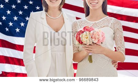 people, homosexuality, same-sex marriage and love concept - close up of happy married lesbian couple with flower bunch over american flag background