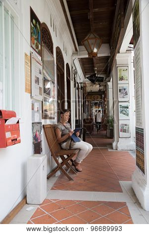 SINGAPORE - CIRCA FEBRUARY, 2015: Arab Quarter (Kampong Glam) is the oldest historic shopping district of Singapore, is popular for visiting tourists. Caucasian woman looking at the tablet PC.