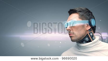 people, technology, future and progress - man with futuristic glasses and microchip implant or sensors over gray background and laser light
