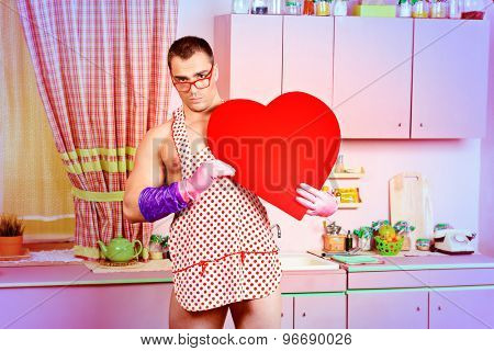 Handsome muscular man in an apron holding big red heart. Pink kitchen. Love concept. Valentine's day.