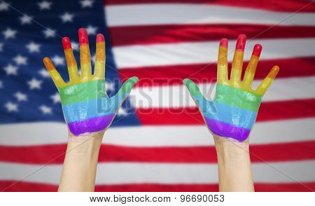 people, gay pride and homosexual concept - palms of human hands painted in rainbow colours over american flag background
