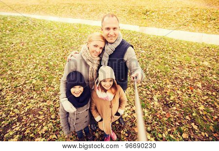 family, childhood, season, technology and people concept - happy family photographing with selfie stick in autumn park