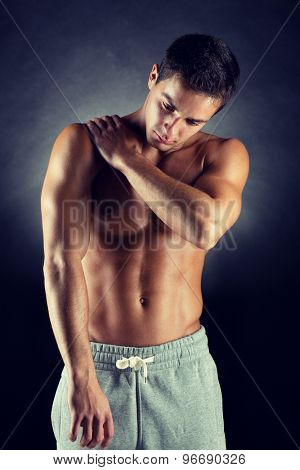 pain relief, sport, bodybuilding, health and people concept - young man standing over black background