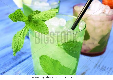 closeup of a glass with an appetizing mojito on a rustic blue wooden table with other different mojitos