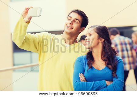 friendship, education and people concept - group of smiling students making selfie with smartphone outdoors