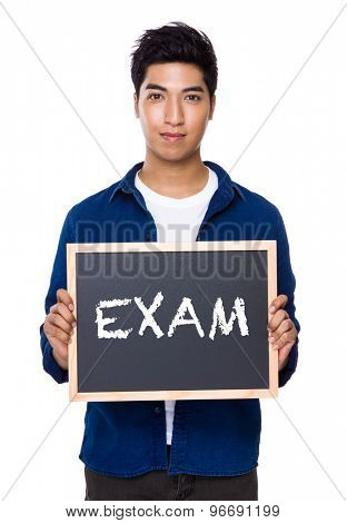 Indian man with chalkboard showing a word exam