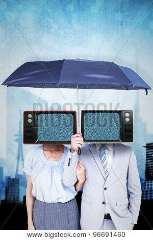 Business people holding a black umbrella against artistic cityscape design