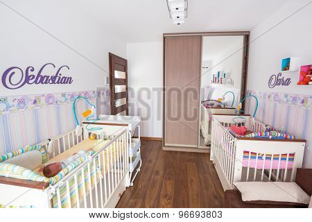 Baby twins room with pastel wallpapers and white cradles