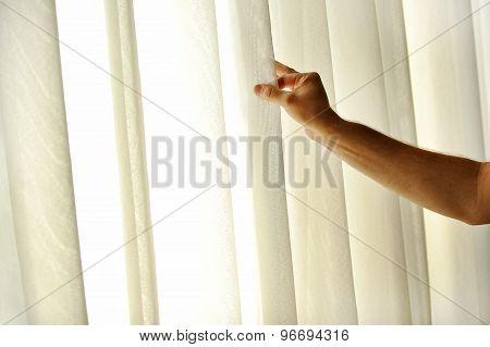 Man's Hand Pulling A Window Curtain