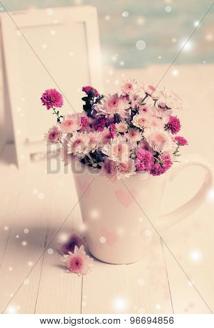 Beautiful flowers in cup on table on light background