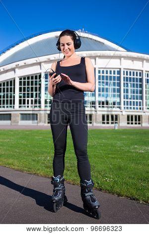Cheerful Girl In Roller Skates Listening Music In Park
