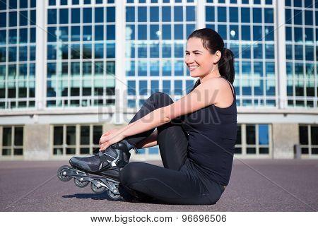 Happy Sitting Woman On Inline Skates